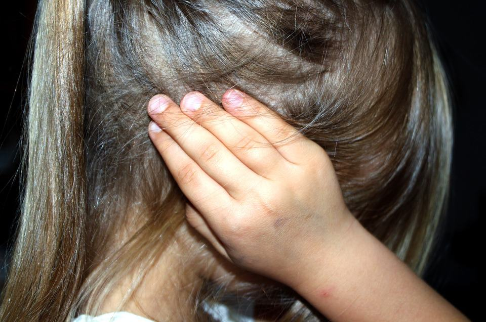 A child covers her ears in frustration over custody.